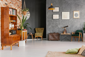 Posters on concrete wall in retro apartment interior with wooden cabinet, armchairs and pillows. Real photo