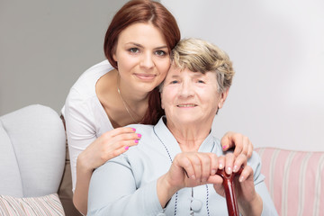 Happy grandmother with walking stick and hugging her smiling daughter