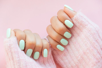 Poster de jardin Manicure Tender hands with perfect blue manicure on trendy pastel pink background. Place for tex