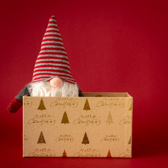 Christmas decoration with a gnome and a gift box on red background