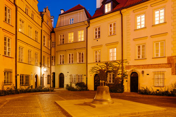 The wishing Bell and old townhouses in Kanonia Square in Warsaw at Night.