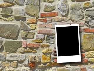 Blank rectangular instant photo frame against weathered stone wall background