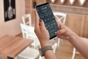 Woman control home temperature and security with phone app, blurred kitchen interior in background