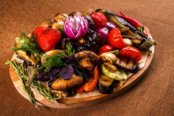 Various grilled vegetables on a round wooden Board. Tomatoes, zucchini, onions, eggplant, mushrooms, paprika