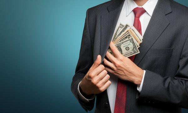 Pocketing company money. businessman placing money into