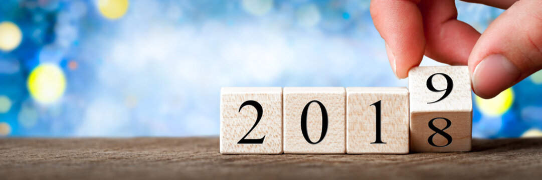 Hand Changing Date From 2018 To 2019 On Wooden Cube Calendar / New Year's Concept
