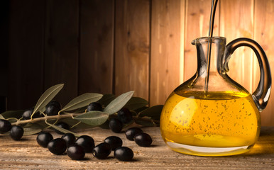 bottle with olive oil on the wooden table