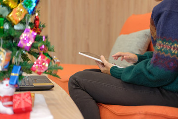 woman sitting on sofa using tablet at home during xmas. christmas holiday new year celebration