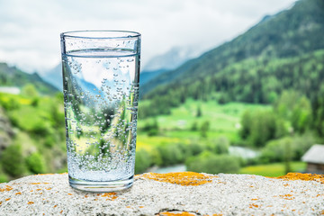 Photo sur Plexiglas Eau Glass of water on the stone. Blurred snow mountains tops and green forests at the background.