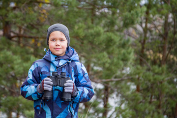 boy with binoculars travels through the forest