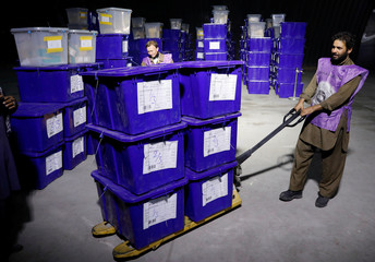 An Afghan election commission worker moves ballot boxes and election material in a warehouse in Kabul, Afghanistan