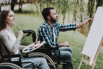 Disabled Young Man on Wheelchairs Drawing in Park.