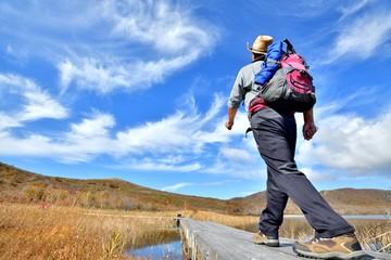 青空の秋・草原を歩くハイカー
