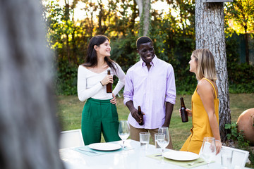 Group of multiethnic man and women standing with beer bottles in green garden near table and chatting
