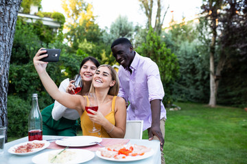 Young diverse friends with wineglasses taking selfie with smartphone gathering in garden for dinner