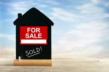 Real estate agent for sale sign and chalk blackboard