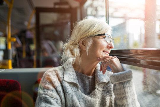 Senior woman looking through bus window