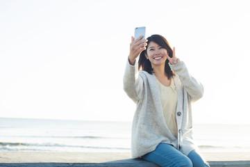 波打ち際で自撮り写真を撮る20代女性