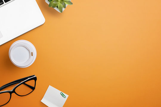 Top view of orange office desk table with laptop, glasses, coffee, plant and sticky note. Flat lay