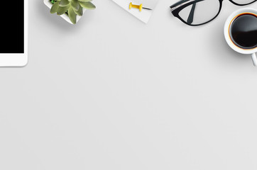 Top view of white office desk table with tablet, glasses, coffee, plant... Flat lay