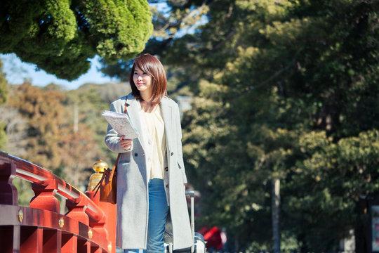 神社を散策する笑顔の20代女性