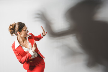 Businesswoman in red suit being harassed, symbolic picture