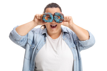 Overweight woman holding donuts infront of her eyes