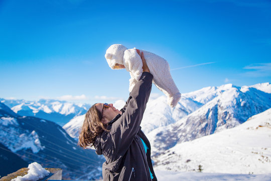 Cheerful woman with baby in snowy mountains