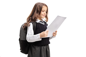 Happy little schoolgirl looking at a test
