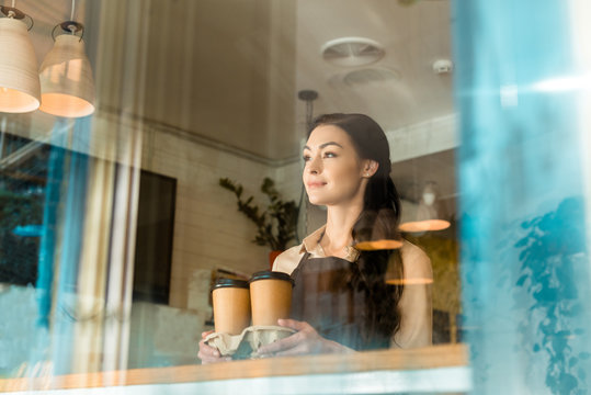 low angle view of beautiful waitress in apron holding coffee in paper cups and looking away in cafe