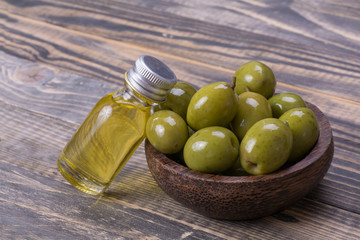 olive oil with olives in wooden bowl on wood background