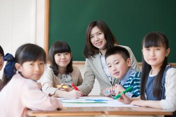 絵を描く小学生と先生