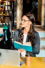 beautiful businesswoman reading book during break on restaurant terrace