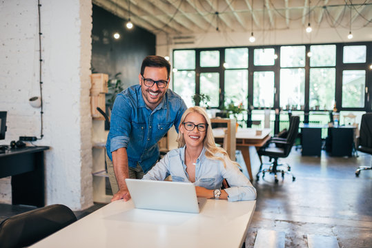 Successful startup business. Portrait of two young smiling people at work in modern office.