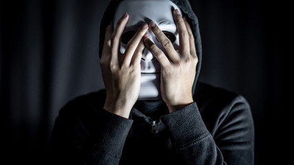 Mystery hoody man wearing white mask in the dark room. Anonymous social masking. Major depressive disorder or bipolar disorder. Halloween concept