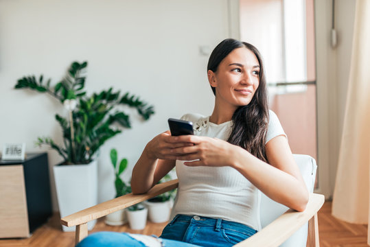 Portrait of a casual young woman using smart phone at home. Looking away.