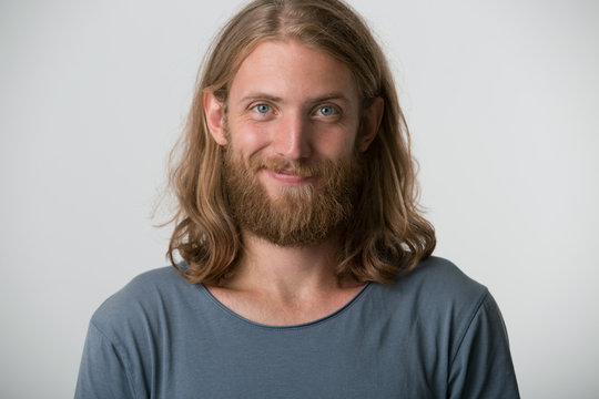 Closeup photo of young guy with a beard, blond hair to the shoulders and blue eyes looking happy one corner of the lips is raised in a smile, isolated over white background.