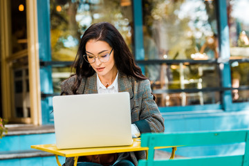 female freelancer working with laptop at restaurant terrace
