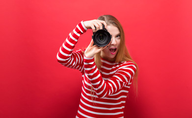 Young woman holding a camera on a solid background