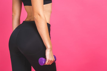 Close-up of sporty woman does the exercises with dumbbells. Photo of sporty woman in sportswear on white background. Strength and motivation. Isolated over pink.