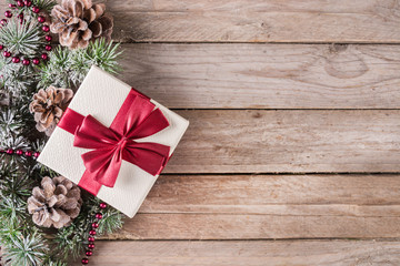 Christmas background with present box with red bow and pine cone and fir tree with snow on retro wooden background. Space for text and design. Close up, selective focus