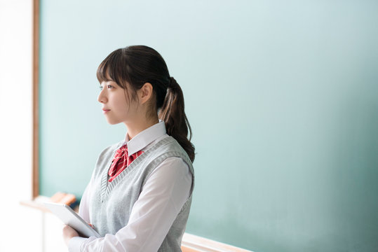 黒板の前でタブレットPCを持ち微笑む女子学生