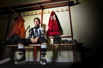 Happy boy sitting in ice hockey dressing room