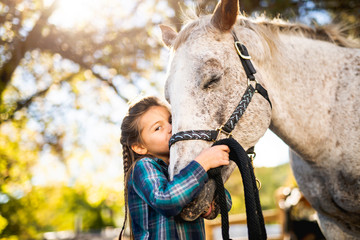 in a beautiful Autumn season of a young girl and horse Wall mural