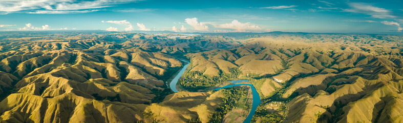 Panoramic view river, hills. Aerial drone shot. Indonesia. Spectacular landscape of Sumba island. Blue sky with white clouds . Beauty of wild untouched nature.