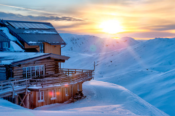 Beautiful winter panorama with wooden mountain cabin.