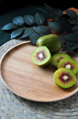 Pieces of Fresh Red Kiwifruit on Wooden Plate