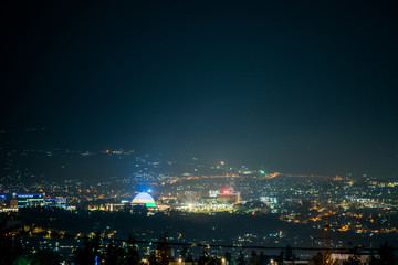 A wide view of city lights on the hills at night, with Kigali Convention Centre lit up in the colours of the Rwandan flag