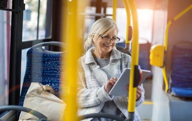 Senior woman using tablet, while riding public bus