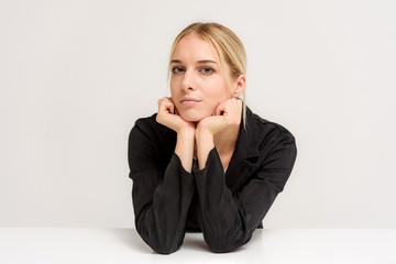 Studio photo of a beautiful blonde girl talking on a white background at the table.
